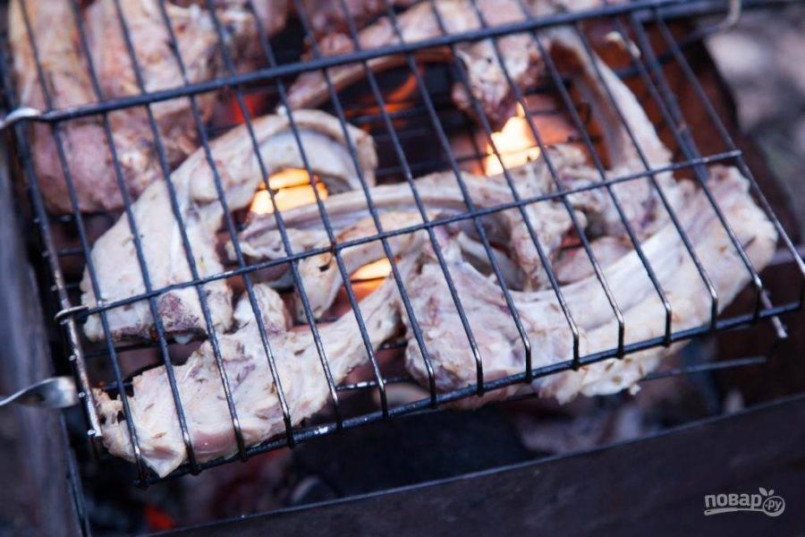 Затем с корейки стряхните маринад. Выложите мясо на сетку на разогретом мангале.