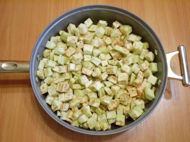 4. На сковороде разогреваем растительное масло. Кладем баклажаны, солим, перчим, добавляем орегано и чили. Закрываем крышкой и жарим на медленном огне до мягкости.