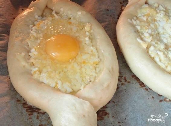 Достаньте полуготовые хачапури из духовки и вбейте в каждое углубление по сырому куриному яйцу. Поставьте хачапури в духовку еще на пять минут. Готовое блюдо посыпьте рубленной зеленью.