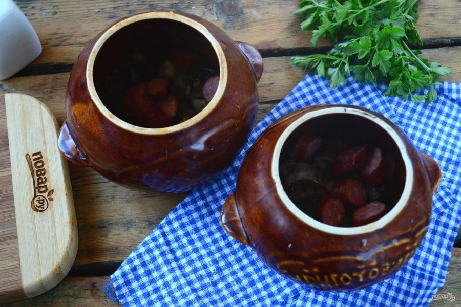 На дно горшочков для запекания положите обжаренные грибы с луком и охотничьи колбаски.