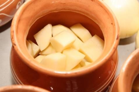 Картофель порежьте кусочками и сложите в горшочек.