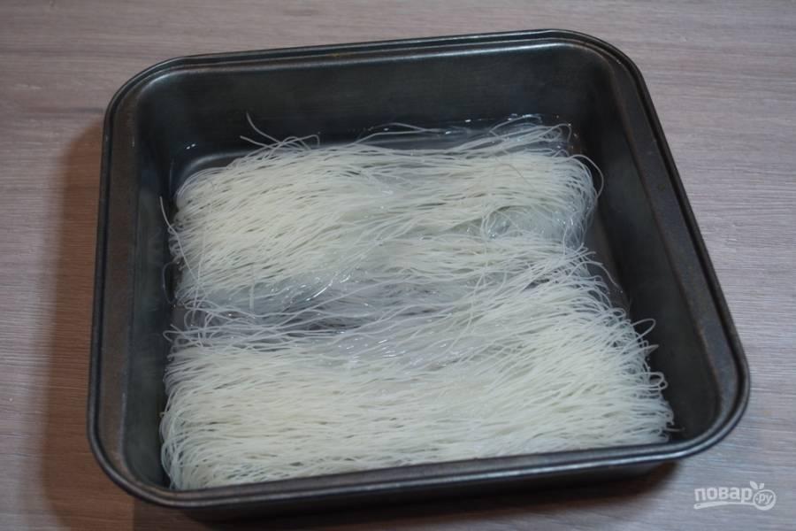 Вскипятите воду. Кипятком залейте рисовую лапшу. Дайте лапше набухнуть. Пока лапша набухает, поставьте на огонь сотейник или вок. Разогрейте.