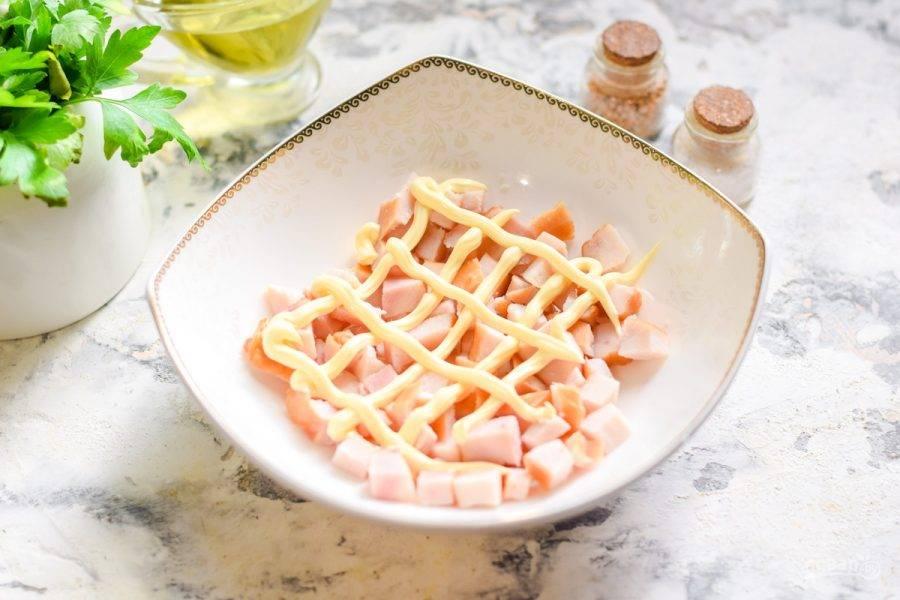 Собираем салат. Первый слой — куриная грудка, смажьте ее майонезом.