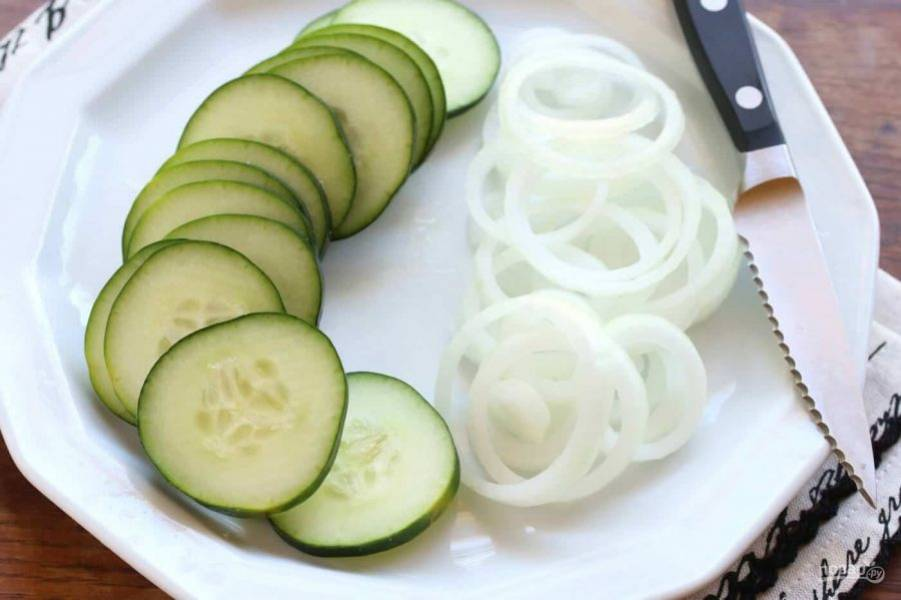3.Вымойте огурцы, очистите чеснок, нарежьте овощи тонкими кольцами.
