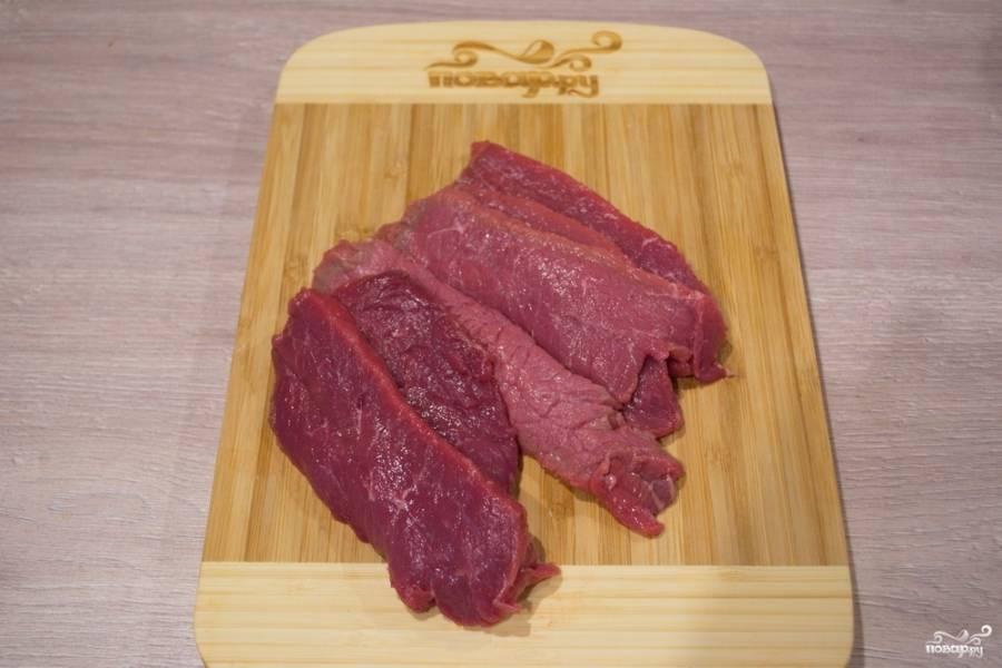 Мякоть говядины нужно обработать, удалив жилы и пленочки. Чистую мякоть нарезаем на пластины. Отбиваем деревянным молоточком.