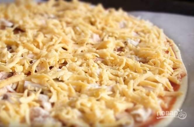6. Смажьте тесто соусом, выложите куриное филе, грибы и сверху уложите сыр. Выпекайте пиццу 10 минут при температуре 220-250 градусов.