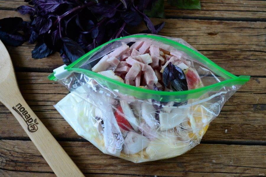 Ветчину, помидор и гриб мелко порежьте, литья базилика порвите на несколько частей. Все эти ингредиенты положите в пакет.