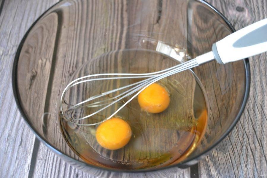 В миску вбейте два яйца, добавьте растительное масло, взбейте в эмульсию с помощью венчика.