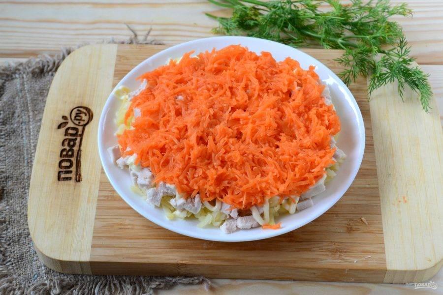 Морковь натрите на мелкой терке и выложите следующим слоем, снова покройте небольшим количеством майонеза.