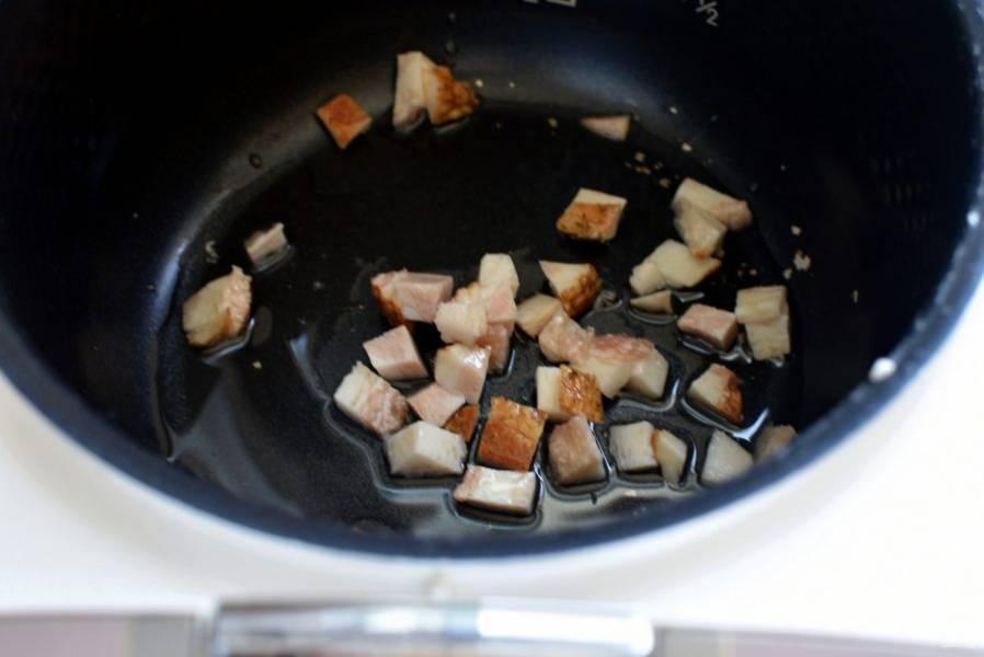Нарежьте копченую грудинку  мелкими кубиками и распустите ее в чаше мультиварки с маслом до прозрачности.
