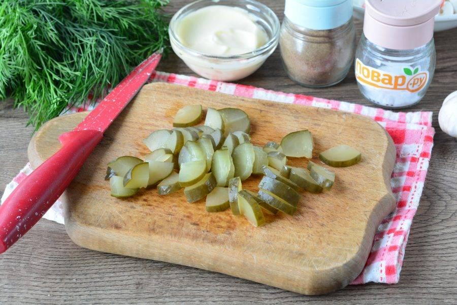 Нарежьте соленые огурцы средними кусочками.