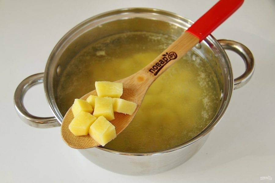 Как только вода закипит, добавьте в кастрюлю нарезанный кубиками картофель и варите его 5 минут после закипания.