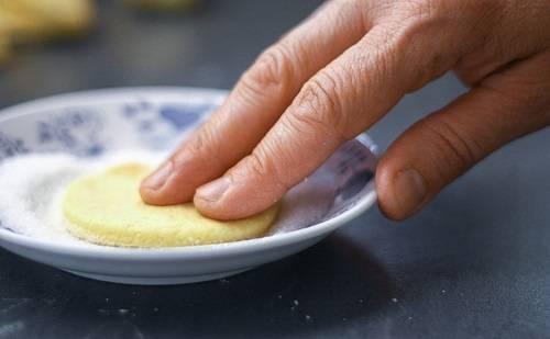 2. С помощью выемок или стакана вырезать из пласта теста кружки среднего размера. Подготовить небольшую мисочку, в которую насыпать сахар. Чтобы печенье из творога Треугольники в домашних условиях было более ароматным, в сахар можно добавить ванилин или щепотку корицы. Кружочек теста окунуть в сахар.