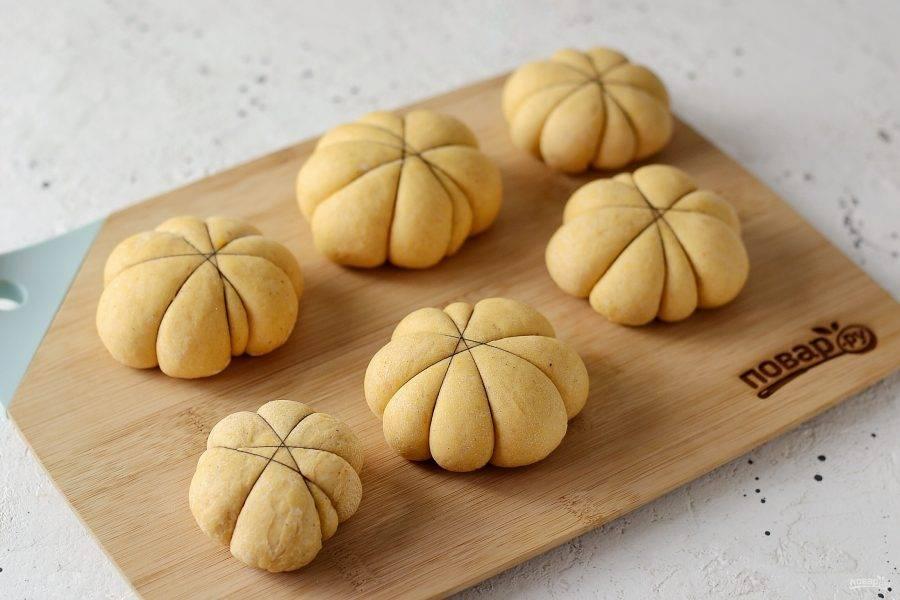 Перетяните булочки нитками, чтобы это напоминало тыквы. Подождите, пока булочки немного увеличатся в размерах (10-15 минут). Духовку разогрейте до 180 градусов, поставьте булочки, при выпечке убавьте температуру до 160 градусов. Выпекайте булочки 17-20 минут.