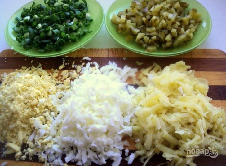 3.В отдельных сотейниках отварите яйца и картофель до готовности. Очистите картошку от кожуры и натрите на терке. Очистите яйца и отделите белок от желтка, затем натрите на мелкой терке по отдельности. Нарежьте мелко зеленый лук, а маринованные огурцы нарежьте мелким кубиком.