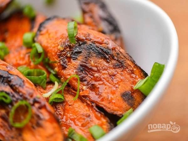 4. Готовую морковь на гриле в глазури выложите в тарелку, вылейте остатки соуса и перемешайте как следует. Присыпьте по желанию измельченной зеленью и подавайте к столу.