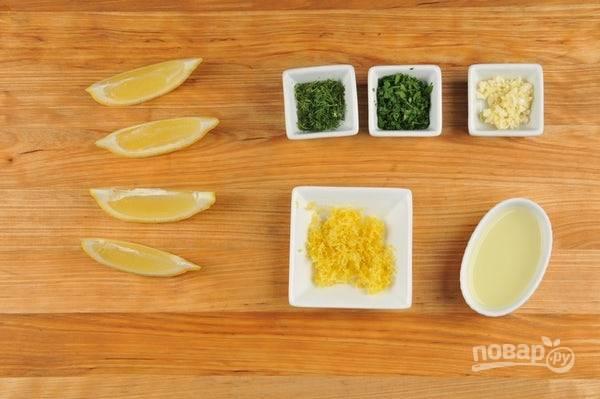 1. С половинки лимона натрите цедру и выжмите сок, а оставшуюся часть разрежьте на дольки. Мелко нашинкуйте петрушку, лук и чеснок.