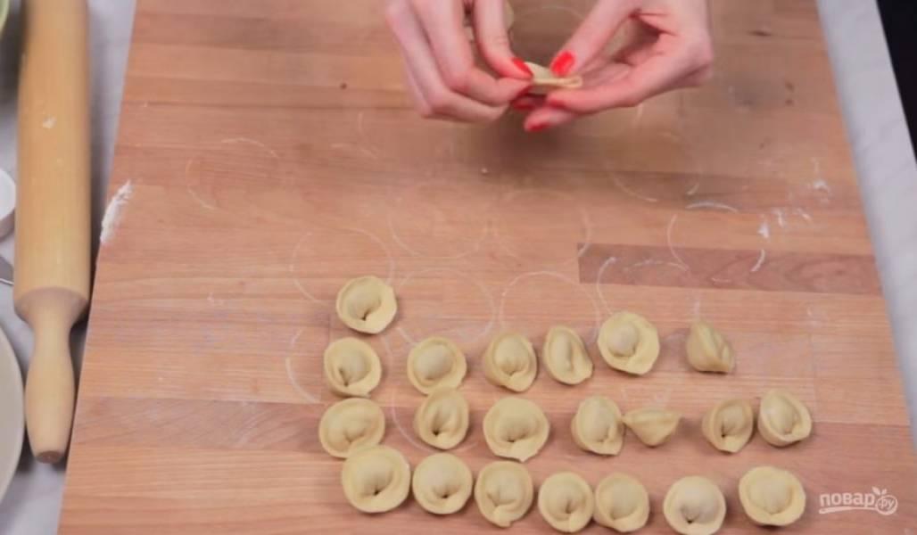3. Тесто разделите на две части и раскатайте в тонкий паст. Вырежьте небольшие кружочки и на средину положите начинку. Затем сформируйте пельмени, закрепив края и защипнув их.