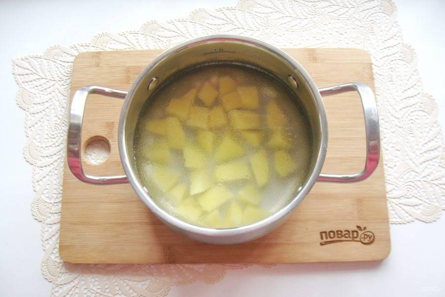 Картофель очистите, помойте, нарежьте кубиками, но не очень мелко. Добавьте в кастрюлю с бульоном. Поставьте кастрюлю на плиту.