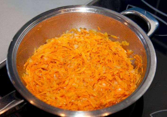 Морковь трем на крупной терке и выкладываем к луку, продолжаем жарить овощи, периодически помешивая.
