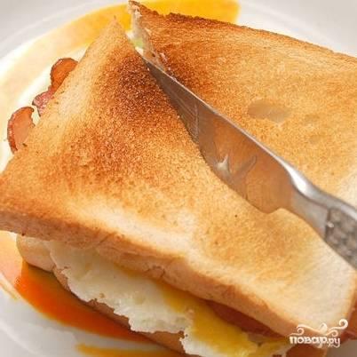 3. Накройте хлеб с яйцом и беконом второй половинкой хлеба и разрежьте пополам, чтобы вышло два треугольника.