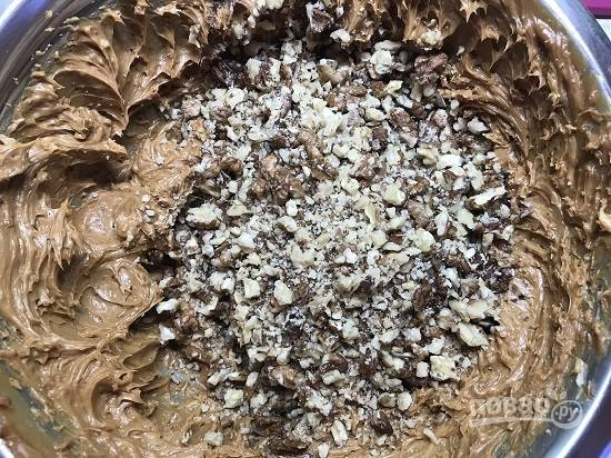 4. Высыпаем в смесь масла и сгущенки орехи, перемешиваем.