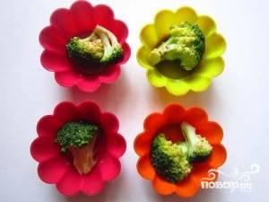 Возьмите одну форму или несколько формочек для выпечки. Смажьте их маслом. На дно выложите брокколи, а сверху залейте сырной смесью до самого верха.