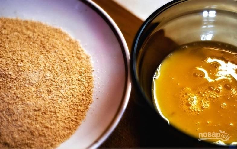 Взбейте яйцо в отдельной миске. В другой смешайте сухари и специи.  Держите обе миске под рукой возле плиты.