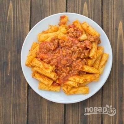 Разделите макароны между тарелками и добавьте оставшийся мясной соус сверху.