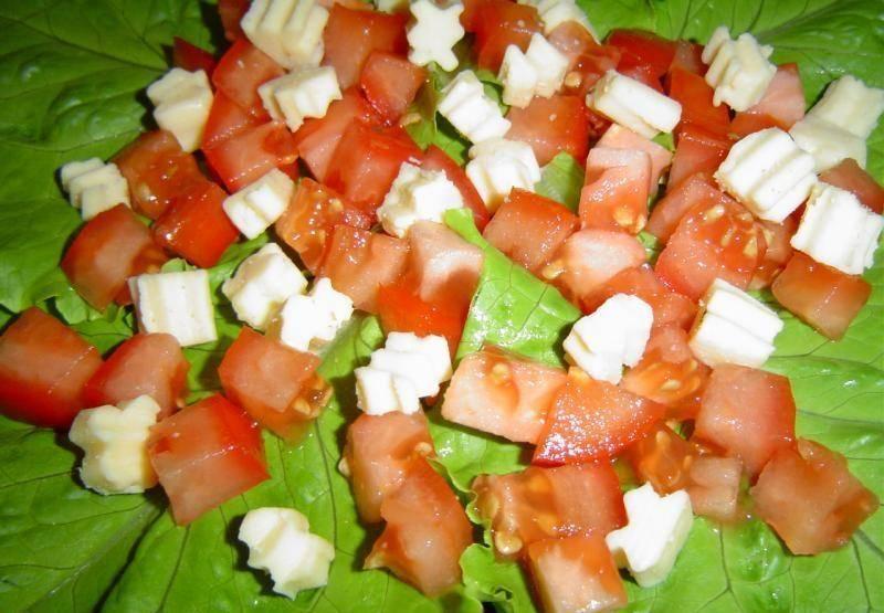 4. На большую тарелку сначала уложите листья салата по кругу так, чтобы они покрыли всю поверхность тарелки. Сверху на них выложите половину нарезанных помидоров, равномерно распределяя их по тарелке, а затем половину сыра.