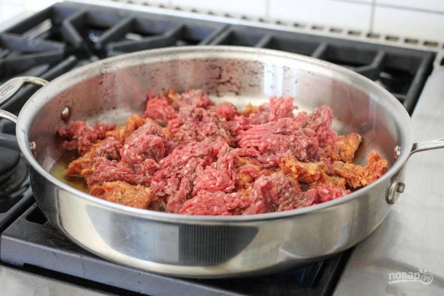 На сковороде разогрейте масло. Добавьте в него фарш и измельченные сосиски.