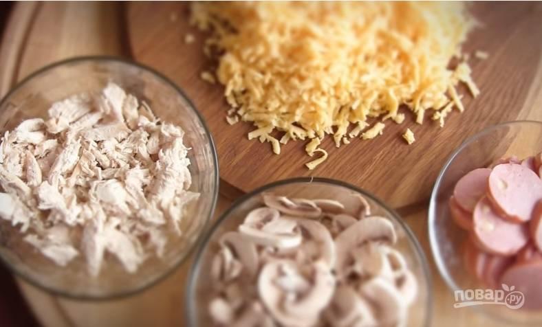 3. Подготовьте начинку. Филе курицы нарежьте небольшими ломтиками, сосиски или колбасу — кольцами. Грибы нарежьте пластинками, а сыр натрите на крупную терку.