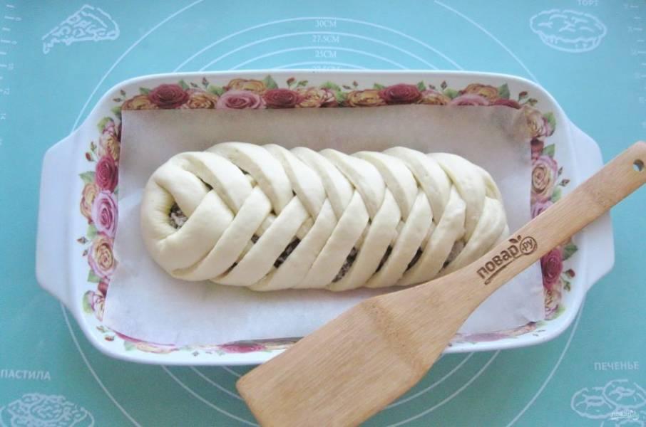 Заплетите кулебяку косичкой и выложите в форму для выпечки с пекарской бумагой.