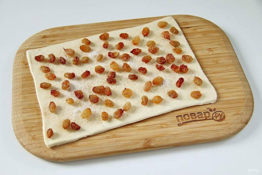 Первый пласт теста раскатайте в форме прямоугольника около 2 мм толщиной. Смажьте поверхность растительным маслом. Соедините сахар с корицей и посыпьте им тесто. Изюм обсушите и разложите сверху.