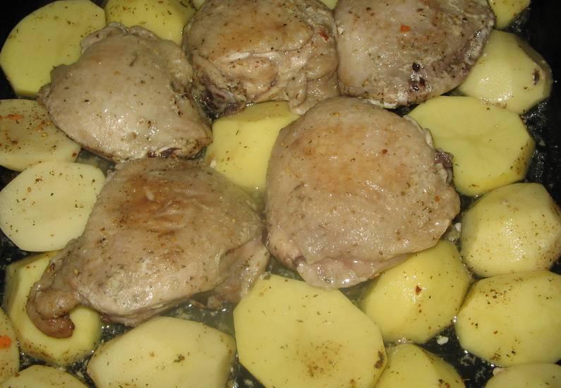 Куриные бедра промойте и обсушите, затем натрите солью, перцем и приправой для курицы, смешанной с майонезом. Оставляем бедра на 2 часа мариноваться, после чего перекладываем их на противень. Отправляем в разогретую духовку, а уже через 15 минут добавляем к ним картофель, порезанный кубиками. Температура 200 градусов.