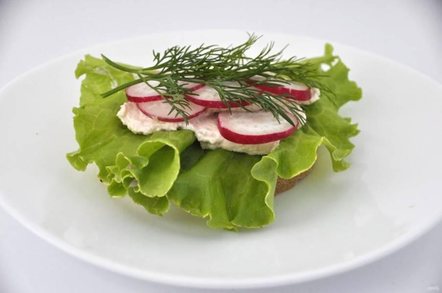 Первый вариант бутербродов: хлеб, салатный лист, крем-фиш, редиска, порезанная колечками, веточка укропа.