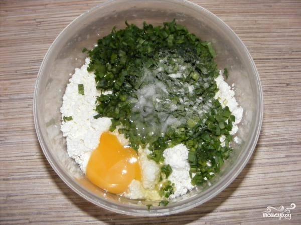 4. Соедините творог с зеленью, добавьте яйцо и соль по вкусу. Выложите чеснок и при желании добавьте щепотку перца. Все как следует перемешайте.