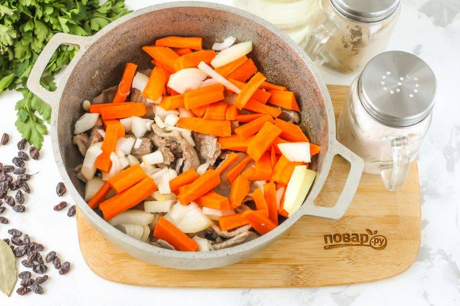 Пока мясо жарится, очистите овощи от кожуры, промойте в воде. Нарежьте морковь брусочками, а лук — полукольцами и добавьте к обжаренному мясу. Томите все на умеренном нагреве до румяности примерно 2-3 минуты.