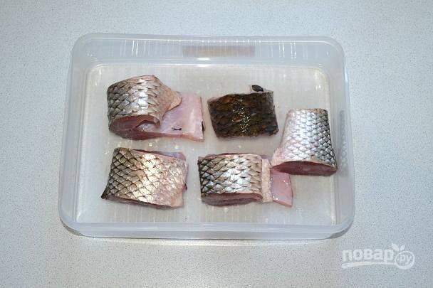 Рыбку промойте, очистите, удалите хвост и голову. Тушку нарежьте небольшими кусочками и выложите в контейнер, в котором будете мариновать рыбку.