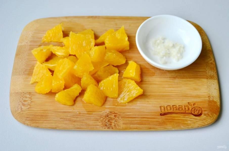 Очистите чеснок, мелко порубите ножом или пропустите через пресс. С апельсина снимите кожуру, удалите белые перепонки, порежьте каждую дольку на 3-4 части. Сладкий перец очистите от семян и порежьте такими же кусочками по размеру.