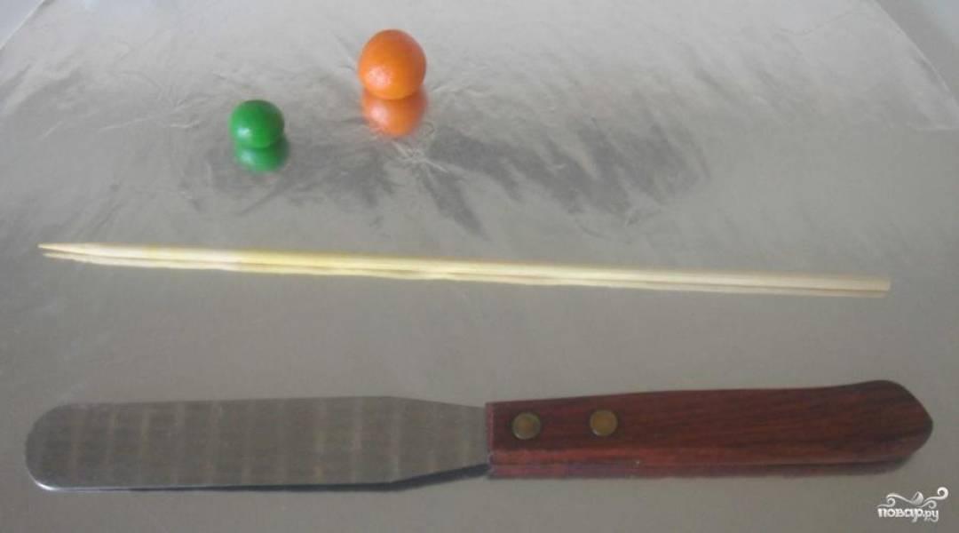 Разделить полученную массу на 4 равных части. 3 части окрасить в оранжевый цвет, тщательно перемешивая тесто. 1 часть таким же образом окрасить в зеленый. От основных комков оторвать шарик побольше для самой морковки и шарик поменьше для ботвы. Приготовить зубочистку и нож для дальнейших манипуляций.