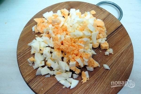 6. Готовые яйца остудите немного, очистите и нарежьте кубиками. Вымойте и измельчите зелень.