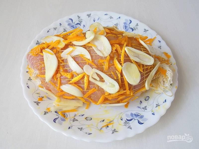 Оставшийся чеснок порежьте тонкими пластинами, цедру тонкой соломкой. Натрите мясо оставшейся солью со всех сторон. Посыпьте чесноком и цедрой.