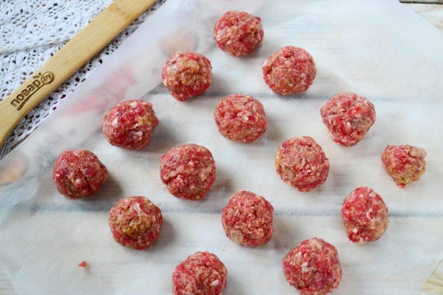Фарш хорошенько перемешайте, сформируйте из него небольшие шарики диаметром примерно 3 см, выложите на противень, застеленный пергаментом и запекайте в духовке при температуре 200 градусов 15-20 минут.