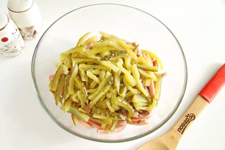 Затем нарежьте соломкой маринованный огурец, слега отожмите его от влаги и добавьте к остальным ингредиентам.