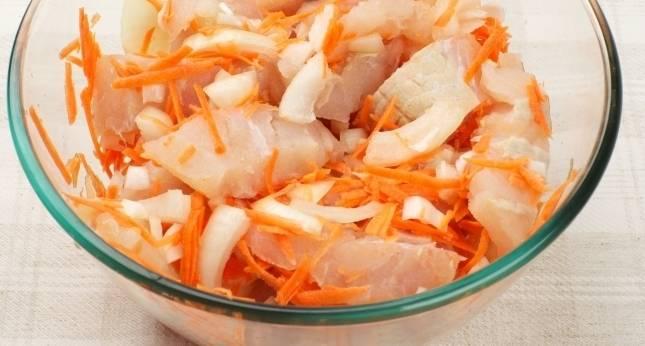 2. Нарезаем мелко лук и шинкуем на среднюю  терку морковь. Теперь нарезаем и рыбу. После этого смешиваем филе с овощами, солим и перчим по вкусу.