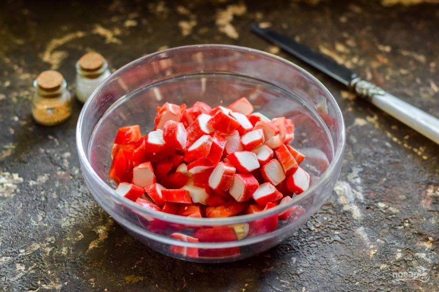 5. Крабовые палочки нарежьте небольшими кусочками, добавьте в салат к остальным ингредиентам.