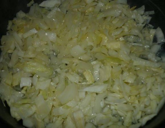 2. На сковороду с высокими бортами или в сотейник выложить капусту. Отправить на огонь и тушить до мягкости.