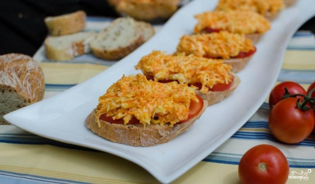 На каждый кусочек хлеба выкладываем по два ломтика помидора, сверху намазываем морковно-сырную смесь, выкладываем бутерброды на блюдо, украшаем зеленью и подаем к столу.
