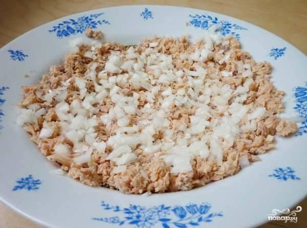 2. Очистите и измельчите лук. Распределите его сверху. Также в рецепте приготовления рыбного салата с рисом можно использовать зеленый лук. Подсолите по желанию и добавьте щепотку перца.